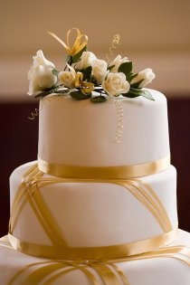 white fondant wedding cake with gold ribbon